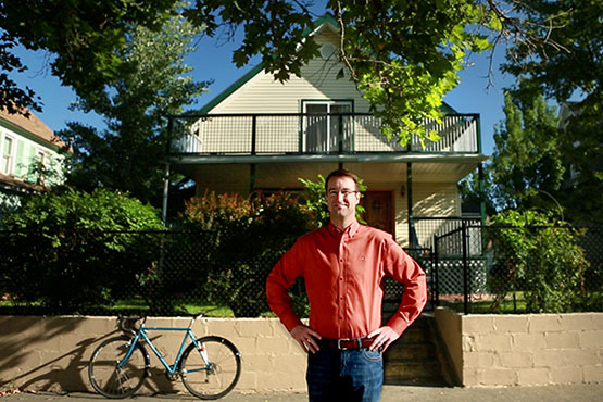 Photo of Keith Kelly in front of a house he renovated