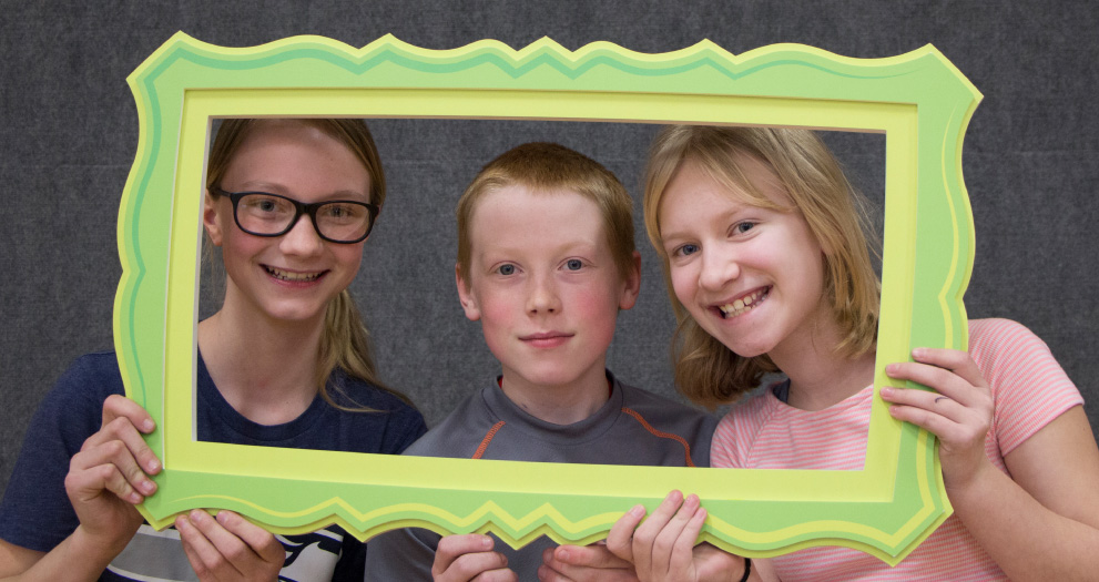 Three kids holding up a picture frame