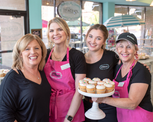 A photograph of the Sweet Frostings Blissful Bakeshop staff, proudly showing a plate of fresh cupcakes.