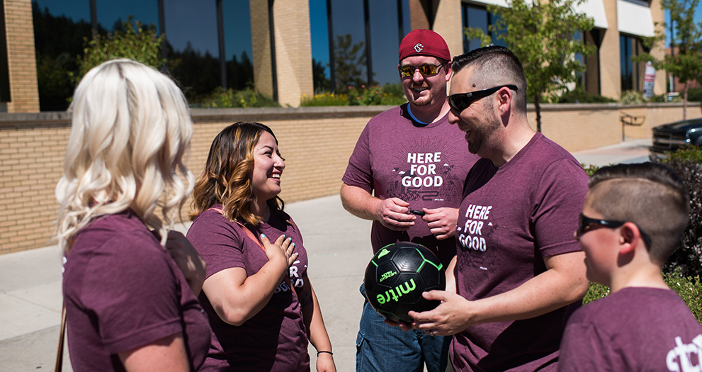 "A photo of STCU employees, wearing their ""Here for good"" tshirts."