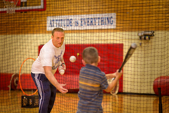 Coach Rick Harris tossing a baseball to a young boy with a bat